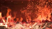 decadência : Burning coals in the stove are mixed creating a fiery dust. Slow motion.