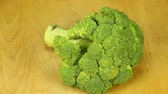 single broccoli : Broccoli rotates on a wooden boards background