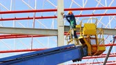 construction worker working at construction site using lifting boom machinery Vídeos