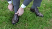men : Man tying patent leather shoes on the grass.