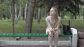 charming : Young woman sitting on a park bench. Some girls are sitting by passers Stock Footage