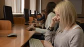 sério : Cheerful student working on the computer. A group of young people in a computer classroom. Young woman with blond hair smiling