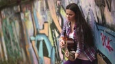 corner : Girl with long hair and a plaid shirt playing guitar against a wall with graffiti.