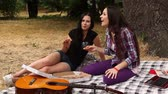 doba jídla : Two girls sit in the shade under a tree eating pizza and talking emotionally.