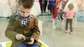 city : Boy with a smartphone. Waiting in the store. Stock Footage