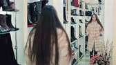 jacket : Beautiful brown-haired girl chooses a fur coat in the store. Shopping. Series.