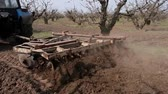 hoe : Tractor cultivating the ground with a disc harrow in the fruit garden