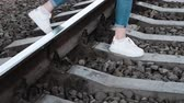confiança : Slim womans legs are bravely crossing the railway