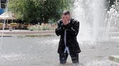 bol : A man is walking in a fountain, covering his face with hands and feeling all the sadness in the world