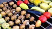street view : A close view of well-cooked mushrooms and vegetables on skewers, lying on a brazier. Street food. Stock Footage