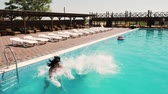 mutlu : A cheerful couple runs and jumps into the swimming pool Stok Video
