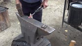 The blacksmith manually forging the red-hot metal on the anvil in smithy Dostupné videozáznamy