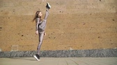 пилатес : Young Beautiful Athletic Girl Gymnast with Steep Stretch. She goes and does leg in split. Dressed in her slinky jumpsuit with picture scales Cobra. On a brown background concrete wall. Slow motion