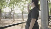 kocogás : Chubby Asian woman standing holding a water bottle after exercise