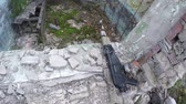 airsofter with automatic rifle climbs out the window of abandoned house. First-person view