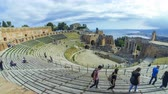 sicílie : TAORMINA, ITALY - MAY 15, 2018: Ruins of ancient Greek theater in Taormina, Sicily, Italy. Coast of Giardini-Naxos bay of Ionian sea and Mount Etna in smoke on the background. Time Lapse. 4K UltraHD