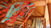 リボン : Ribbons swaying in the wind on the porch of a wooden house 動画素材