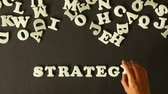 focus : A person spelling Strategy with plastic Letters Stock Footage