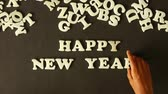 ano : A person spelling Happy New Year with Plastic Letters