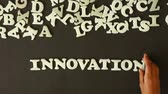 invent : A person spelling Innovation with plastic letters