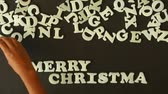 ano : A person spelling Merry Christmas with plastic letters Vídeos