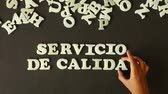 slib : A person spelling Quality Service with Plastic Letters (In Spanish)