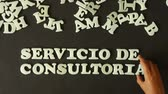 management : A person spelling Consulting service (In Spanish) with plastic letters