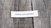 slib : A Quality over Quantity paper sign on wood background