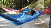 alvás : Woman relaxing in a Hammock