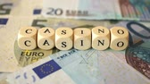 финансы : A dolly shot of several euro bills and the word casino written with small wooden dices.