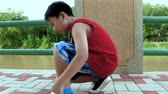 шнурки : Pan video around asian boy runner in sportswear sitting and learning to tie his sport shoe. Do it yourself concept. Outdoors with bright sunlight on summer day. Healthy Lifestyle.