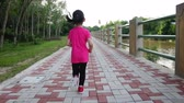 yourself : Back view. Asian girl runner in sportswear sitting and wearing her sport shoe and jogging in the park. Outdoors with bright sunlight on summer day. Healthy Lifestyle. Stock Footage