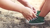 bondade : Kindness mother helping her daughter to tie shoelaces. Child wearing green sport shoes. Concept about care and good relations in happy family with kids. Outdoor on summer day.