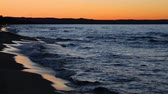 yansıma : Loop features waves splashing on the Michigan coast of Lake Superior with a colorful sunset sky reflected upon wet beach sand. Stok Video