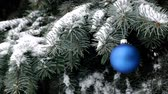 Blue Christmas ball hanging on branch of spruce under a snowfall
