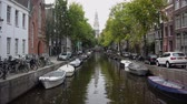astarlı : View of a boat lined canal in Amsterdam with a steeple in the background. Stok Video