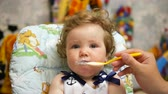 distances : Happy baby in her favorite house. Feeding baby with a spoon. Stock Footage