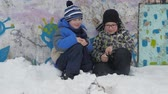 irmãos : winter bonfire smoke. Winter fire. Two small boys sit squatting and watch the smoke firecrack burn. A boy with glasses on the street. Vídeos