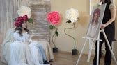 şakayık : artist draws a portrait from nature. The artist draws a portrait from nature. Floating camera focus, camera in motion. Beautiful model, with a wreath of scarlet peonies on his head, posing sitting in a white armchair. girl model admires her way on canvas. Stok Video
