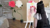 şakayık : artist draws a portrait from nature. The artist draws a portrait from nature. Floating camera focus, camera in motion. Beautiful model, with a wreath of scarlet peonies on his head, posing sitting in a white armchair. Stok Video