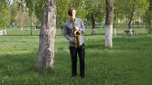 viyola : young man plays the saxophone. man is standing on the green grass and walking among the birches. Stok Video