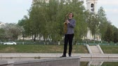 původní : young man plays the saxophone. The musician plays on the wind instrument, walks the parapet to the camera, the camera is in motion. Man moves on the narrow road. man on the background of the city bridge, river, temple and high-rise buildings.