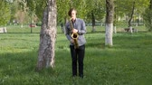 sax : young man plays the saxophone. man is standing on the green grass and walking among the birches. Stock Footage