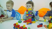 developing : Childrens developing a game room. Emotions of young children during entertaining classes. Children build buildings from plastic and wooden geometric figures.