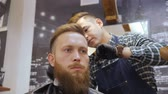 barber beard : Hairdresser for men. Barbershop. Caring for the beard. Barber with hair clipper works on hairstyle for bearded guy barbershop background. Hipster lifestyle concept. Barber with clipper trimming hair on nape of client. Hipster client getting haircut. haird Stock Footage