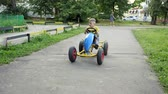 wheeled : Child rides on cycle mobile. child is driving a car. Slow motion