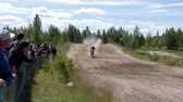 rivet : June 10, 2018 Russian Federation, Bryansk region, Ivot - Extreme sports, cross motocross. The motorcyclist enters the turn on the race track. Dirt is flying from under the wheels. The machine overcomes obstacles. Athletes fly through the air. slow motion
