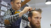 mužskost : Hairdresser for men. Barbershop. Hair care. Hairdresser with a haircut works for a hairstyle for a bearded guy. The concept of a hipster lifestyle. The hairdresser cuts the hair on the back of the client. Customer Hipster gets a haircut. a hairdresser in
