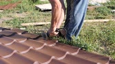 dekarz : Work with roofing material. roof of metal. Cutting profile metal electric bulgarian. Sparks fly from under the metal circle of the hand cutting tool. sheet of roofing material lies on green grass. Cutting sheet iron. slow motion Wideo