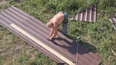big leaf : Work with roofing material. roof of metal. Cutting profile metal electric bulgarian. Sparks fly from under the metal circle of the hand cutting tool. sheet of roofing material lies on green grass. View from a height. Cutting sheet iron.